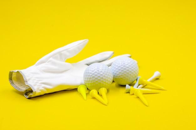 La palla da golf e le t del guanto da golf sono su fondo giallo