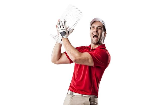 Giocatore di golf in una camicia rossa che celebra con un trofeo di vetro nelle sue mani, su uno spazio bianco.