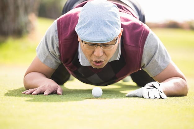 Giocatore di golf che soffia la palla nel buco
