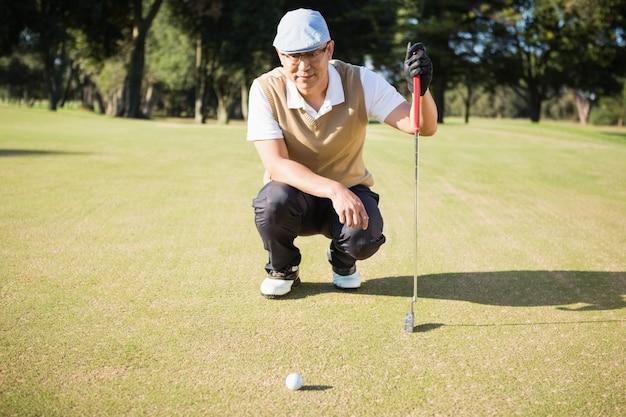 Giocatore di golf che si accovaccia e che guarda la sua palla