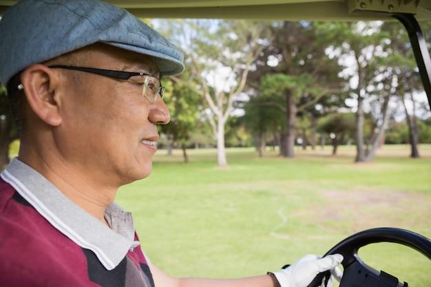 Giocatore di golf che guida un buggy di golf