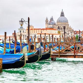 Gondole sulla banchina e la chiesa di santa maria della salute in background, venezia, italy