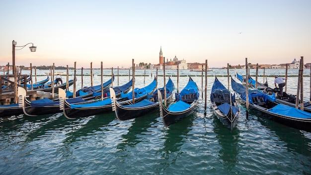 Gondole ormeggiate in piazza san marco con la chiesa di san giorgio di maggiore a venezia, viaggio in italia