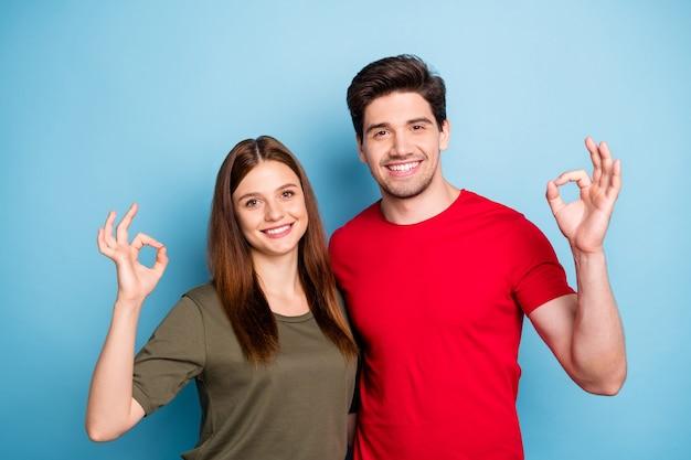 Buone pubblicità! il ritratto di due promotori romantici delle coppie mostra il segno giusto consigliare la promozione eccellente degli annunci indossa la maglietta rossa verde moderna isolata sopra fondo blu di colore