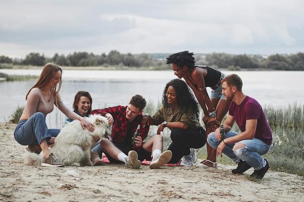Bravo ragazzo. un gruppo di persone fa un picnic sulla spiaggia. gli amici si divertono durante il fine settimana.