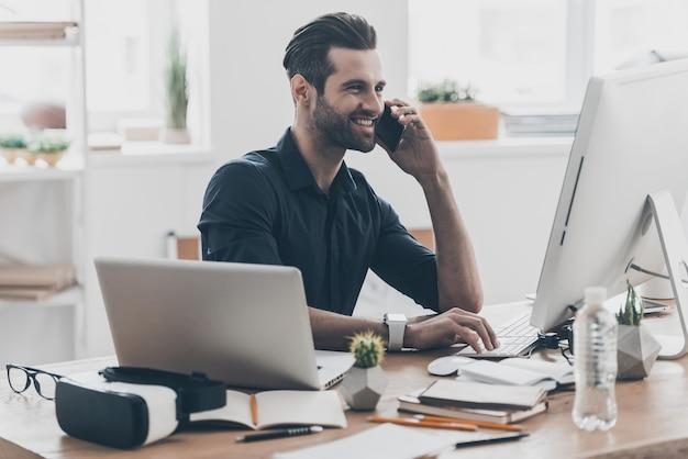 Buone chiacchiere d'affari. bel giovane che parla al telefono cellulare mentre è seduto al suo posto di lavoro in un ufficio creativo Foto Premium