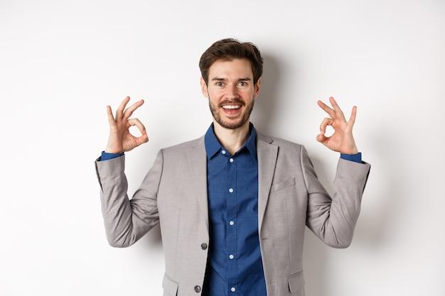 Bella scelta. uomo d'affari sorridente in vestito che mostra segni giusti e sembra felice