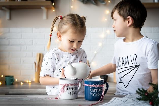 Buongiorno natale. fratello e sorella bevono il tè al tavolo della cucina con i biscotti in cucina. un tempo di miracoli e di appagamento dei desideri. buon natale.