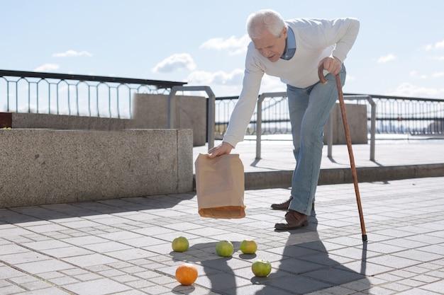 Bravo uomo stanco intelligente che prende il bastone in una mano lasciando cadere e svuotando i frutti sul terreno