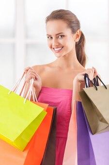 Buona giornata per lo shopping. bella giovane donna in vestito rosa che tiene le borse della spesa e sorride alla macchina fotografica