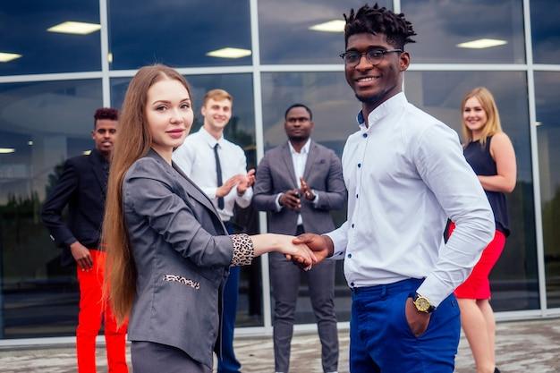 Concetto di buon affare. gruppo multinazionale di giovani imprenditori saluti e stretta di mano con i colleghi in background. bella donna d'affari sorridente con il partner afroamericano che stringe la mano