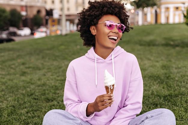 Una ragazza attraente e di buon umore con occhiali da sole rosa, felpa con cappuccio viola e jeans sorride, si siede sull'erba fuori e tiene il gelato
