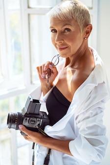 Buona idea. fotografo allegro che mantiene il sorriso sul viso e in piedi vicino alla finestra