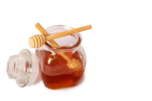 Buon isolato di vasetto di vetro pieno di miele e bastone di legno su sfondo bianco. miele con mestolo di miele in legno. close-up di vetro può pieno di miele e bastoncino di legno su di esso. tracciati di ritaglio. foto in studio