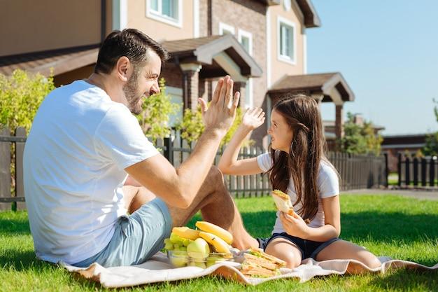 Buon lavoro. allegro padre piacevole e la sua adorabile figlia seduti sul tappeto, mangiando panini e dandosi il cinque a vicenda