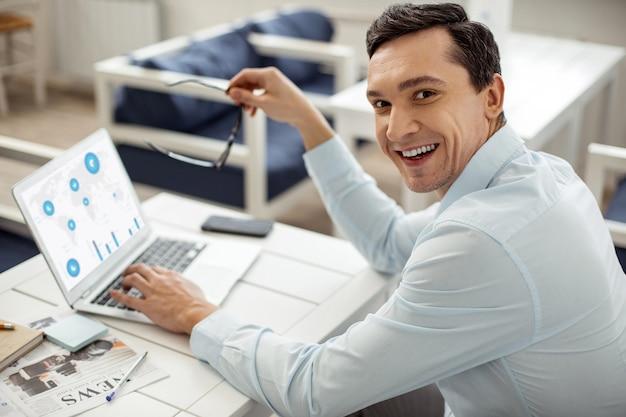 Buon lavoro. uomo dai capelli scuri gioioso bello sorridente e lavorando sul suo laptop e tenendo gli occhiali mentre era seduto al tavolo