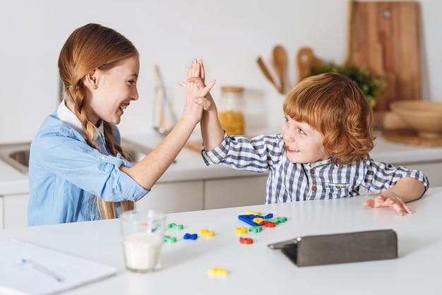 Bel lavoro, piccoletto. divertenti e produttivi adorabili bambini che battono le mani dopo aver trovato un modo per risolvere un'equazione matematica usando speciali numeri colorati sul tavolo