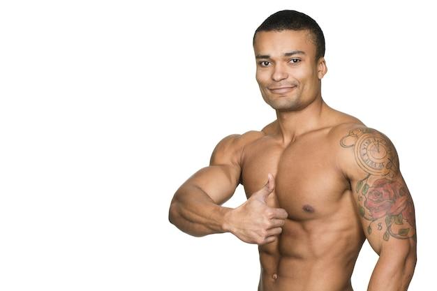 Buon lavoro! ritratto di un uomo africano attraente con il torso muscoloso che mostra i pollici in su e sorridente