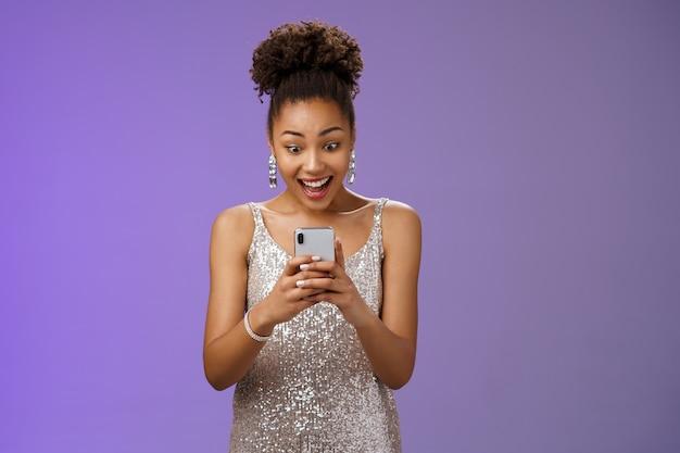Bella donna afro-americana stupita in abito argento lucido sorridente divertito leggendo un fantastico messaggio di notizie smartphone guarda il display del telefono stupito felice sfondo blu. copia spazio
