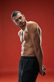 Bell'uomo atleta con un corpo muscoloso al chiuso