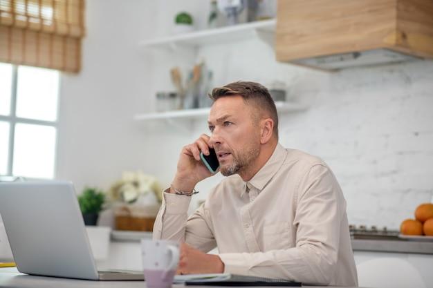 Bell'uomo barbuto seduto in cucina e avendo una chiamata