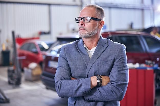 Bell'uomo barbuto in piedi nell'officina riparazioni auto