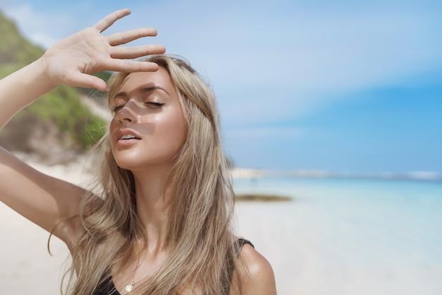 Bella donna abbronzata bionda in posa sulla spiaggia di sabbia vicino all'oceano blu