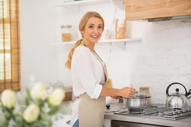 Bella donna bionda che cucina in cucina