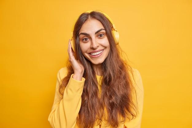 La bella giovane donna castana ascolta la traccia audio