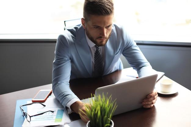 Un bell'uomo d'affari tiene in mano un laptop mentre è seduto in ufficio.
