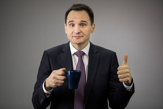 Bell'uomo d'affari in abiti formali, cravatta con tazza di caffè mostrando segno ok