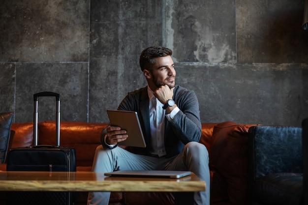 Un bell'uomo d'affari seduto sul divano di un hotel e con in mano il tablet
