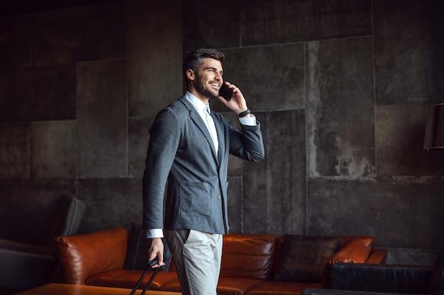 Un bell'uomo d'affari che cammina nella hall di un hotel e fa una telefonata