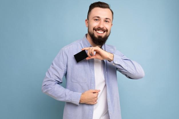 Bello giovane barbuto brunetta sorridente fresco che indossa camicia blu alla moda e maglietta bianca