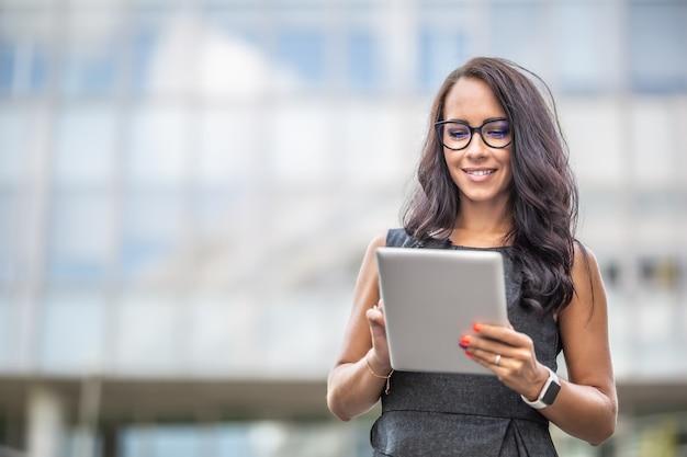 L'imprenditrice di bell'aspetto legge da un tablet sorridendo, camminando all'aperto.