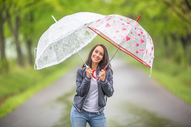 Una bella donna tiene due ombrelli sopra di lei sotto la pioggia durante una passeggiata nella natura.
