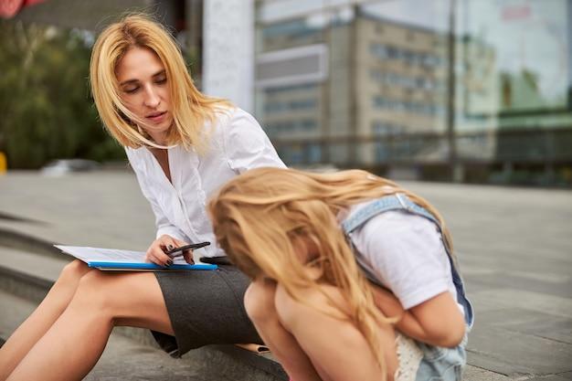 Bella donna che trascorre del tempo con una bambina in città mentre è seduta sui gradini