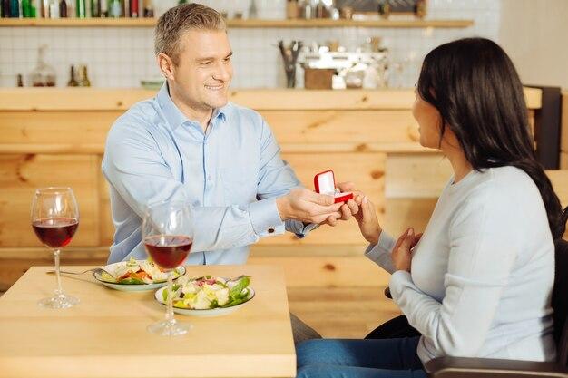 Un uomo di bell'aspetto ispirato e ben costruito che sorride e propone alla sua bella donna handicappata contenta mentre tiene un anello e cenando