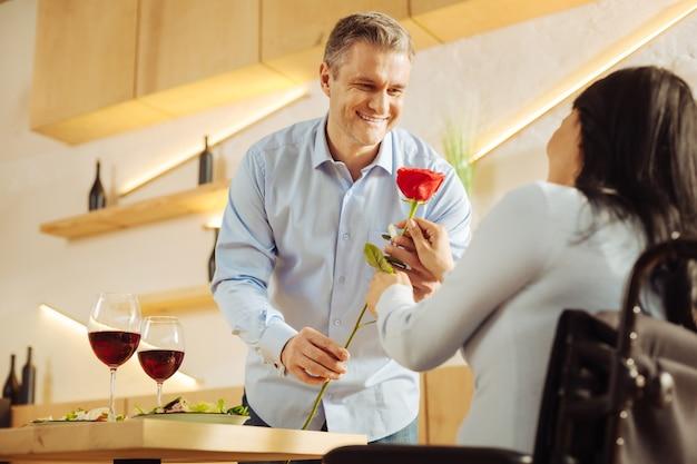 Bell'uomo gioioso e ben costruito che sorride e dà un fiore rosso alla sua amata donna disabile dai capelli scuri mentre mangia una cena romantica
