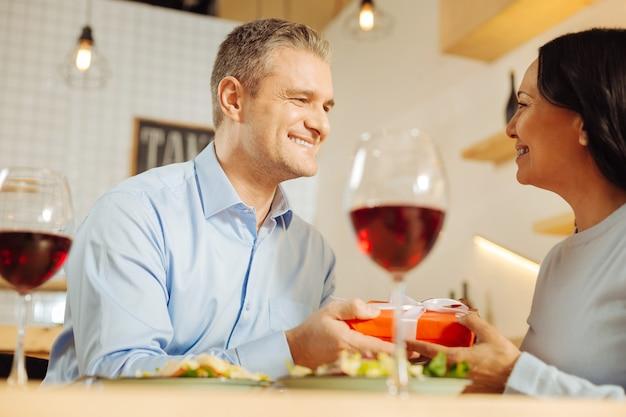 Bell'uomo amorevole ben costruito che sorride e fa un regalo alla sua bella donna dai capelli scuri felice mentre cena romantica