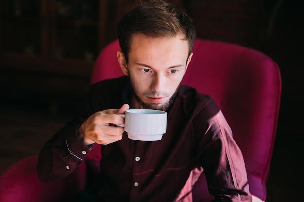 Bell'uomo che beve caffè sulla poltrona
