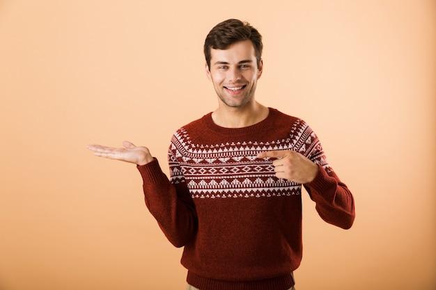 Bell'uomo con setole che indossa un maglione lavorato a maglia che punta il dito contro copyspace sul palmo, isolato sul muro beige