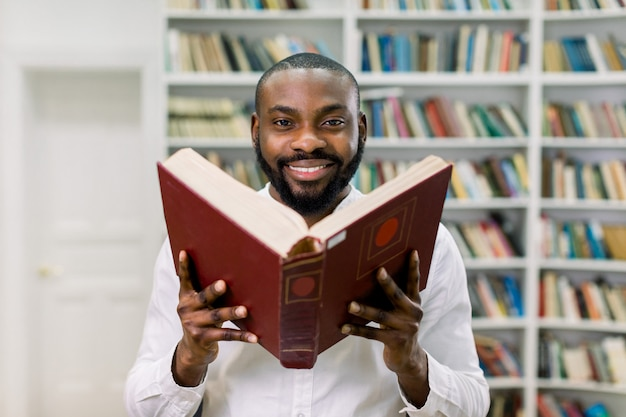 Giovane ragazzo barbuto africano soddisfatto bello in camicia casuale bianca, posante sullo spazio degli scaffali di libro in biblioteca moderna