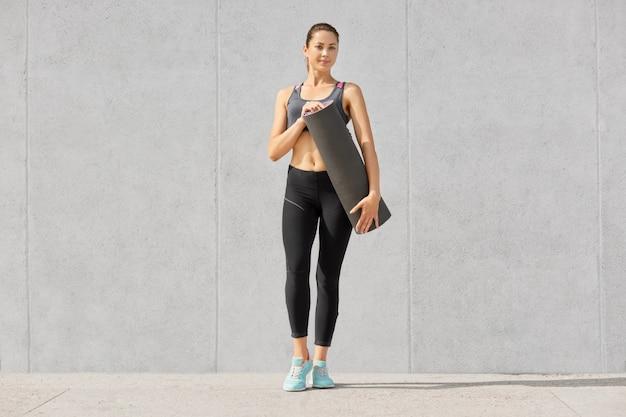 Bella donna snella sportiva vestita in abiti sportivi, detiene tappetino per avere allenamento fitness