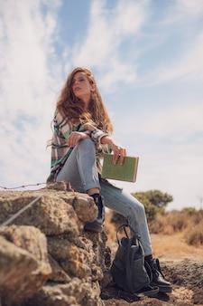 Una bella donna posa seduta in cima a un muro di pietra