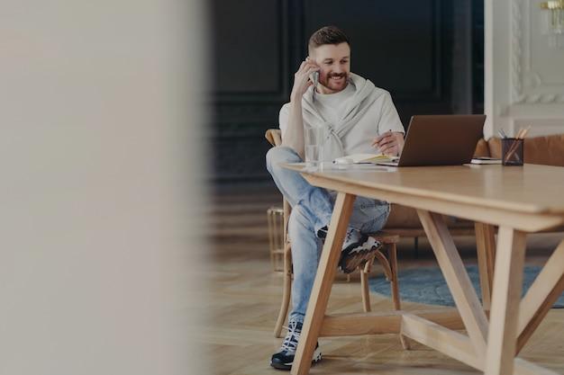 Giovane uomo d'affari di bell'aspetto in abbigliamento casual che parla di lavoro o affari sul telefono cellulare e guarda il monitor sul laptop mentre è seduto alla scrivania di legno in un moderno ufficio o appartamento di lusso