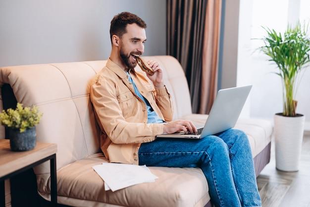 Bello giovane uomo in abiti casual mangia il pranzo mentre si lavora da casa