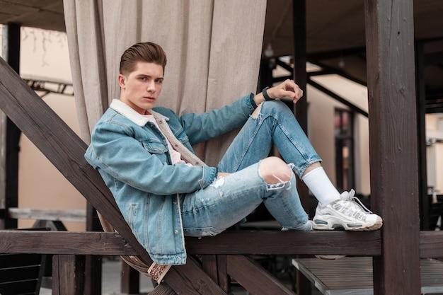 Un giovane di bell'aspetto in abiti casual di jeans blu alla moda in eleganti scarpe da ginnastica bianche si siede sulla ringhiera di legno in città. ragazzo alla moda alla moda in denim vintage giovanile indossare in strada. abbigliamento uomo estivo.
