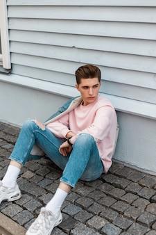 Un giovane di bell'aspetto in felpa rosa alla moda in jeans blu alla moda in scarpe da ginnastica bianche si siede su piastrelle di pietra vicino a un edificio vintage all'aperto in città. ragazzo carino in abbigliamento denim moda giovanile in strada.