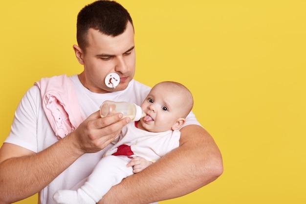 Bello giovane che alimenta la sua bambina isolata sopra la parete gialla, papà caucasico con la bottiglia nelle mani.